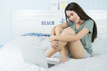 Smiling asian beauty woman sitting on the bed with computer laptop.