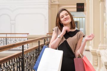 Joyful pretty young woman shopping in a mall