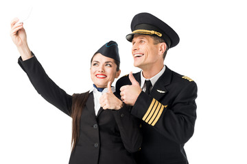 Smiling stewardess and pilot taking selfie isolated on white
