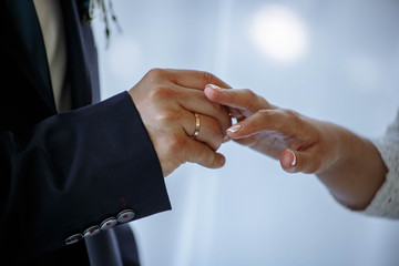 groom puts on an engagement ring to the bride