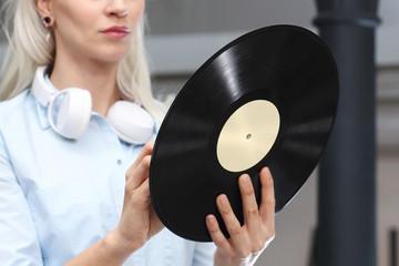 Płyta winylowa. Młoda stylowa kobieta trzyma płytę winylową.