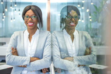 Smiling businesswoman with crossed arms posing in office with reflection in the glass. Wall mural