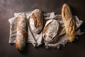 Variety of loafs fresh baked artisan rye and whole grain bread on linen cloth over dark brown texture background. Top view, copy space.