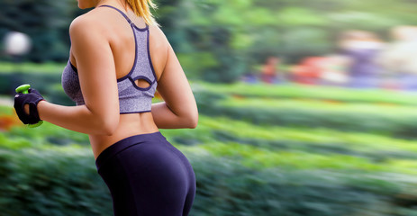 Training concept, young girl running with dumbbells in hands on street. Torso close up. Copy space
