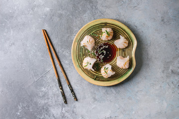 Asian steam potstickers dumplings stuffed by shrimps, served on ceramic plate with soy sesame sauce and chopsticks over grey texture background. Top view, space.