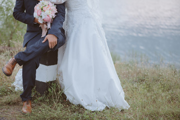 Wedding couple outdoor.Close-up of groom holding bouquet and bride. Wedding couple holding hands near river.