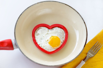 omelet from an egg in a frying pan in the shape of a heart