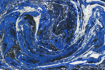 Creative abstract art background in blue, white and black colors. Handmade painted background. Acrylic painting on water. Liquid paint.