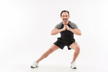 Horizontal photo of muscular man doing workout with stretching legs and sit-ups keeping hands in front of him, isolated over white background