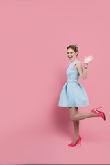 youth woman wearing blue dress and high heels shoes, making a surprised face and looking at camera, while standing against pink pastel background. Say Hooray