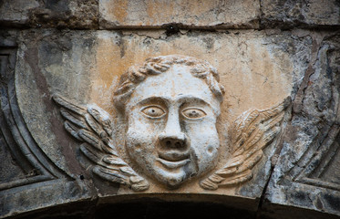 Smiling face of angel on the front of Cathedral of Notre Dame of Assumption in Entraveaux (Alpes de Haute Provence, France)