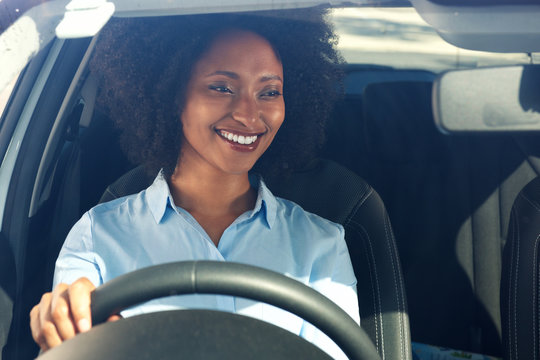 happy young african american woman driving a car and smiling