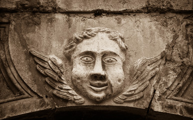 Smiling face of angel on the front of Cathedral of Notre Dame of Assumption in Entraveaux (Alpes de Haute Provence, France). Sepia photo.