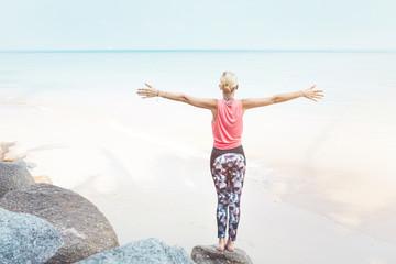 Free happy fitness woman enjoying summer on the beach