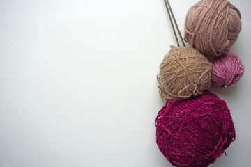 Gray and maroon balls of thread and knitting needles. White background