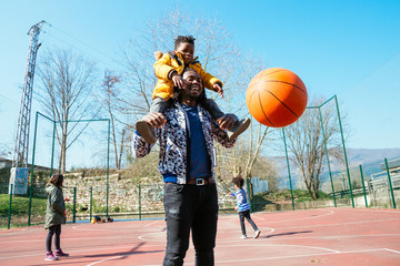 Dad and little son playing basketball