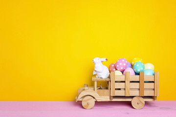 Wooden toy truck with Easter eggs and  bunny in the back on yellow background. Space for text.