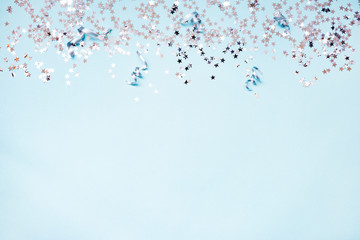 Star shaped silver sequins and silver ribbons over blue background. Copy space.