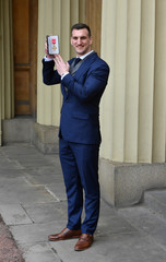 Welsh rugby player Sam Kennedy-Warburton poses after he was awarded his Officer of the British Empire (OBE) medal during an Investiture ceremony at Buckingham Palace, London