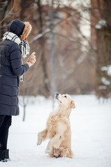 Photo of young woman in black jacket training dog in snowy park