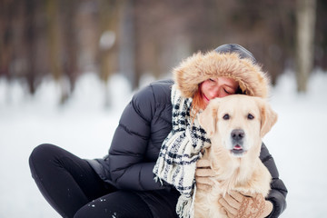 Photo of woman in black jacket squatting next to dog in winter park