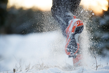 Photo from back of running man in sneakers on snowy forest