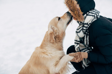 Picture of dog giving paw to woman in black jacket on winter