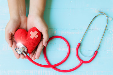 World health day, Healthcare and medical concept. Woman hand holding red heart with Stethoscope,  thermometer and yellow Pill on Pastel white and blue wooden table background texture.