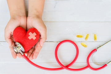 World health day, Healthcare and medical concept. Woman hand holding red heart with Stethoscope, notepad or notebook, thermometer and yellow Pill on white wooden table background texture.