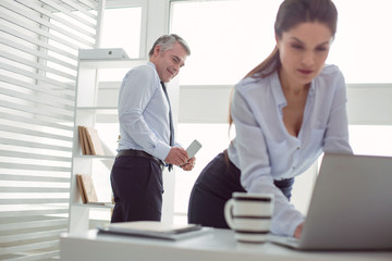 Social problem. Unpleasant happy adult man standing in the office and looking at his secretary while taking photos of her