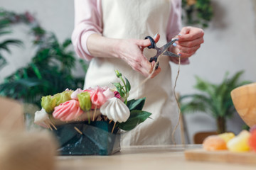 Image of florist with scissor-cutting rope at table with bouquet, marmalade, marshmallow in room