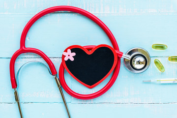 World health day, Healthcare and medical concept. Stethoscope, red and black heart, thermometer and yellow Pill on Pastel white and blue wooden table background texture.