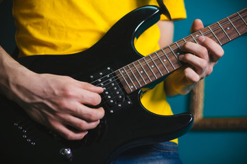 Male hands on the strings of an electric guitar. Playing black guitar closeup.