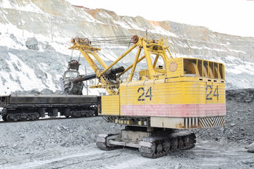 The excavator loads the stones into the cars. Loading ore into the railway cars in the quarry.