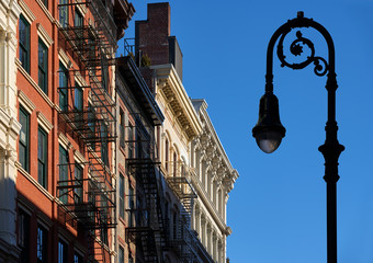 Soho building facades with cornices, fire escapes and a lamp-post. Manhattan, Soho, New York City