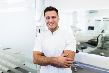 Handsome male dentist in doctors white lab coat posing in modern dental office