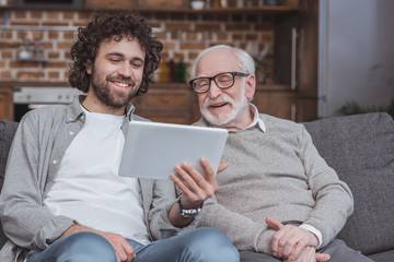 smiling adult son showing something on tablet to senior father at home