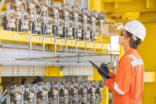 Production operator log record pressure reading value in log book to monitor gas and oil pressure of raw gases produce well, offshore oil and gas wellhead platform maintenance daily activity.