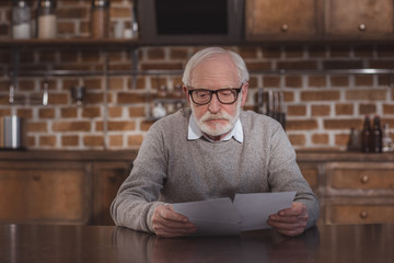 handsome grey hair man sitting at table and looking at photos at home