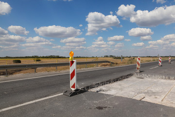 Roadworks, road signs at a highway or road on reconstruction with blue sky and clouds