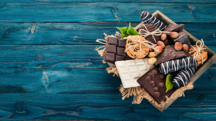 A set of milk chocolate and black chocolate in a wooden box with nuts and biscuits. On a blue wooden background. Copy space for text.
