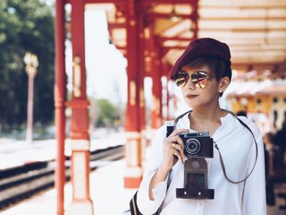 Young traveler woman holding vintage camera in hands.