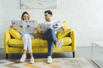Businessman with wife reading newspapers about travel and business while sitting on sofa in modern room with painting