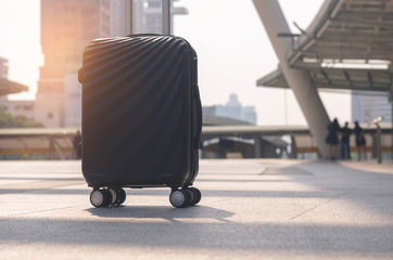 luggage walking on concrete floor at outdoor in the city with sunlight already to go to travel planning in vacation time concept.