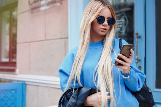 Beautiful young hipster woman using smart phone.Portrait of attractive young woman walking outside and reading text message on mobile phone