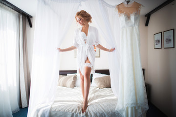 Very beautiful, slender, attractive bride, in lingerie and Bathrobe, going to the wedding and posing in the bedroom of the hotel room.