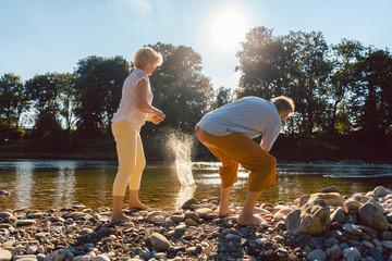 Senioren beim Steine flitschen auf dem Fluss