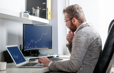 Investor analyzing stock market with charts on screen at home office