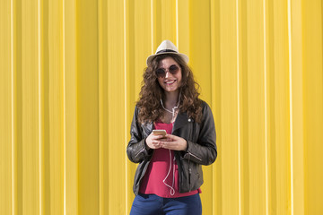 Portrait of a beautiful young woman listening to music on her mobile phone with earphones and having fun over yellow background. Casual clothing. Wearing sunglasses and a modern hat. Happy.