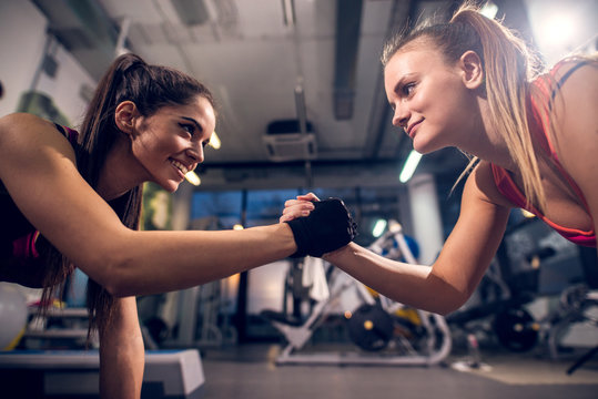 Two young motivated smiling attractive focused sporty active girls while doing push ups and holding hands together in the modern gym.